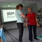 uczestniczka projektu z fizjoterapeutką regulują kije do nordic walking