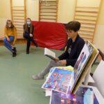 Głośne czytanie w szkole w Wyszanowie. Na zdjęciu dzieci uczestniczący w spotkaniu i pani bibliotekarka szkolna