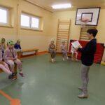 Głośne czytanie w szkole w Wyszanowie. Na zdjęciu dzieci uczestniczący w spotkaniu i bibliotekarka szkolna
